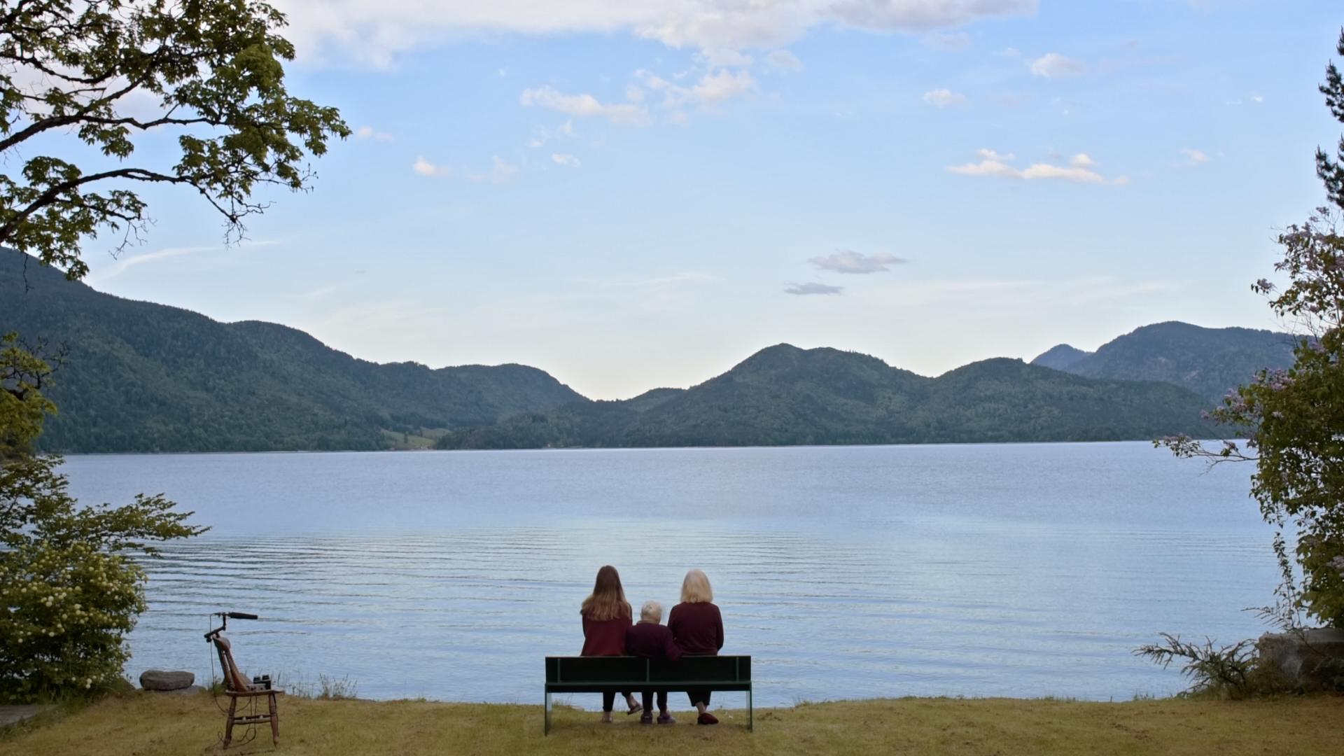 Panoramablick auf See vor Gebirge, auf einer Bank am Ufer sitzen drei Frauen unterschiedlicher Generationen.